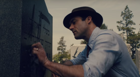 "Morgan Spector, as Herman in the trailer for HBO's ""The Plot Against America,"" cleans a swastika off of a Jewish gravestone. (Screen shot from YouTube)"