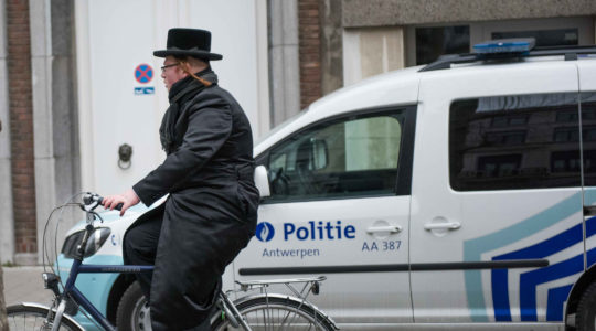 A haredi Jew cycling past a police car in Antwerp, Belgium on March 16, 2016. (Cnaan Liphshiz)