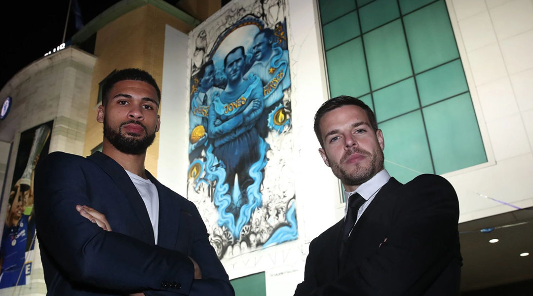 Chelsea soccer players Cesar Azpilicueta, right, and Ruben Loftus-Cheek standing against the club's mural commemorating Holocaust victims in London, UK on Jan. 15, 2020.. (Courtesy of Chelsea FC)