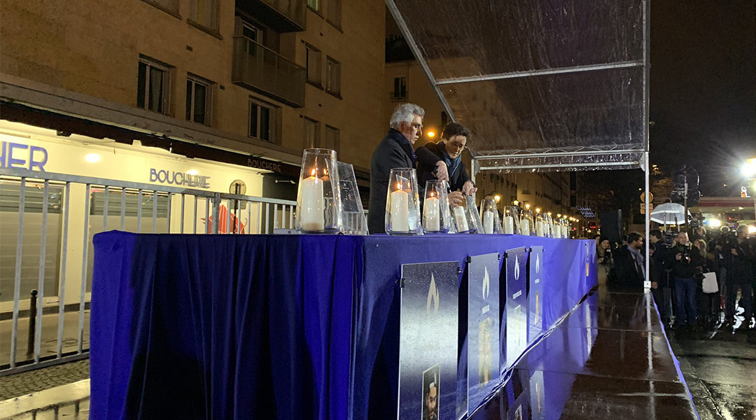 Senior French government official Emmanuelle Wargon and CRIF board member Serge Dahan lighting a memorial candle outside the Hyper Cacher store in Paris, France on Jan. 9, 2020. (Courtesy of CRIF)