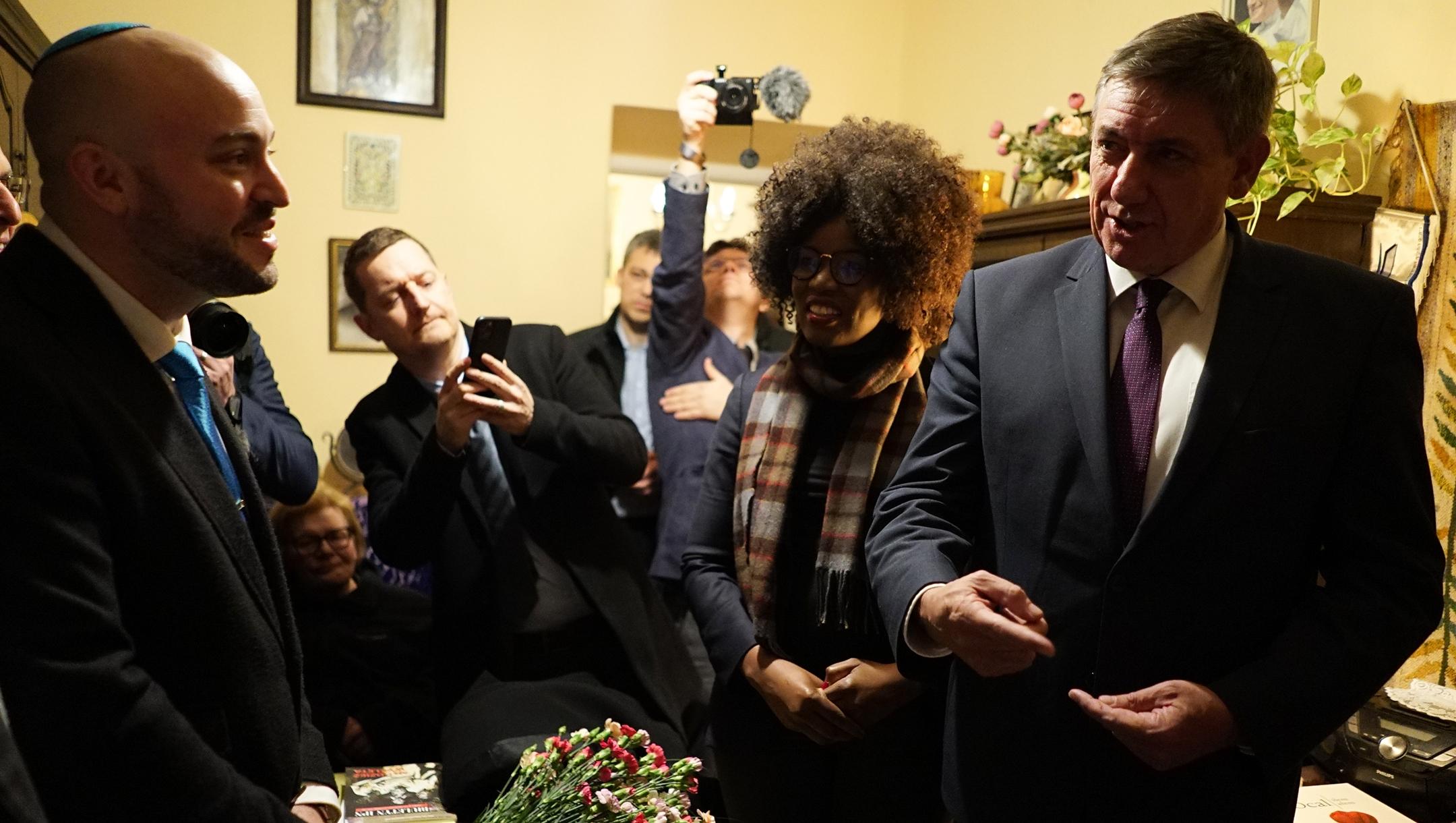 Flemish Prime Minister Jan Jambon, right, Froum the Depths founder Jonny Daniels, left, and members of the Belgian delegation visiting the home of Maria Nowak in Krakow, Poland on Jan. 20, 2020. (Tytus Kondracki)