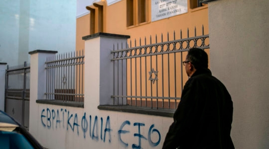 """A man walking past a slogan reading """"Outside the Jewish Snakes"""" on the fence of the synagogue of Trikala, Greece on December 31, 2019.(Lefteris Partsalis/AFP via Getty Images)"""
