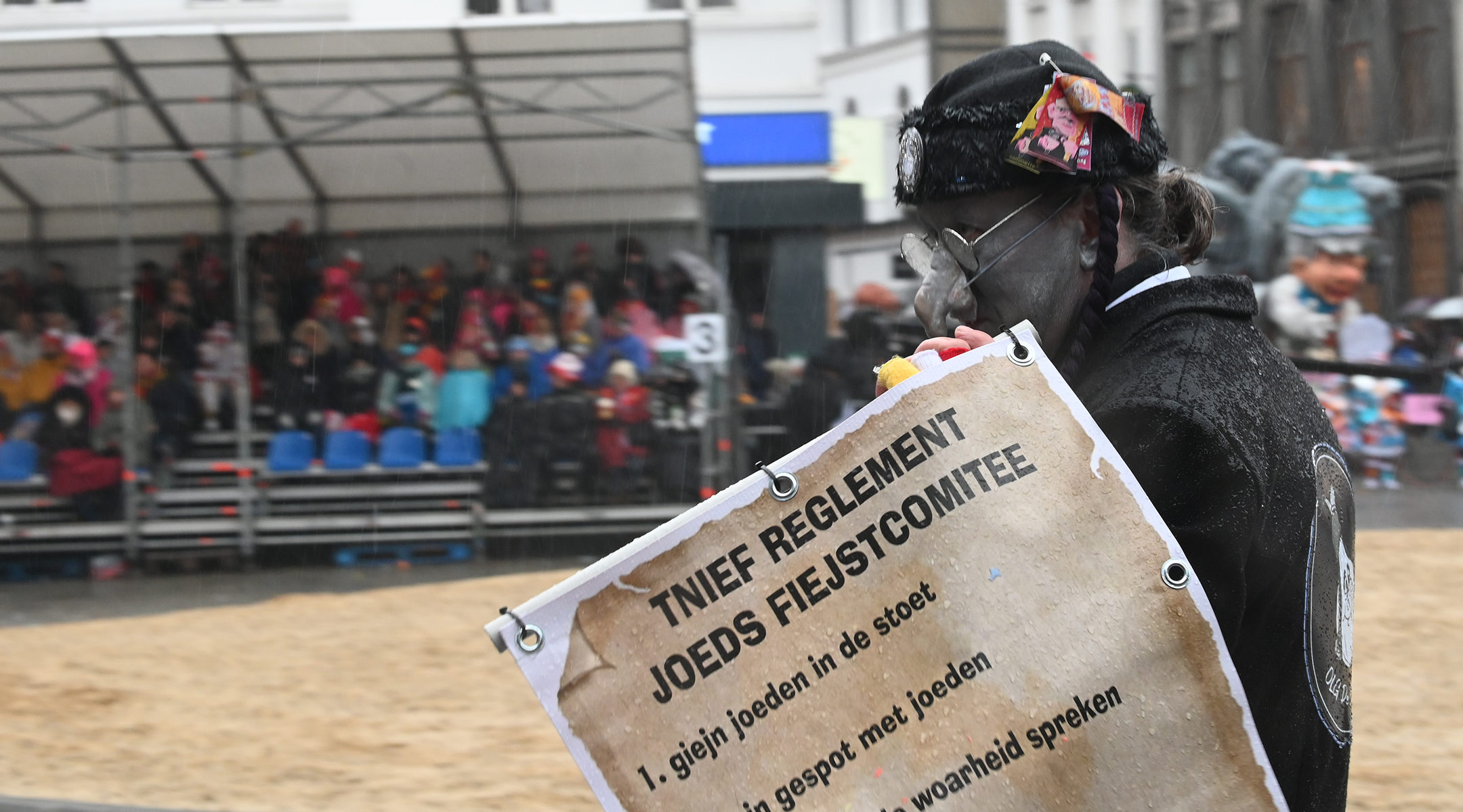 "A man wearing a fake hooked nose and carrying a sign warning readers not to ""tell the the truth about the Jew"" at the annual procession of the carnival in Aalst, Belgium on Feb. 23, 2020. (Cnaan Liphshiz)"