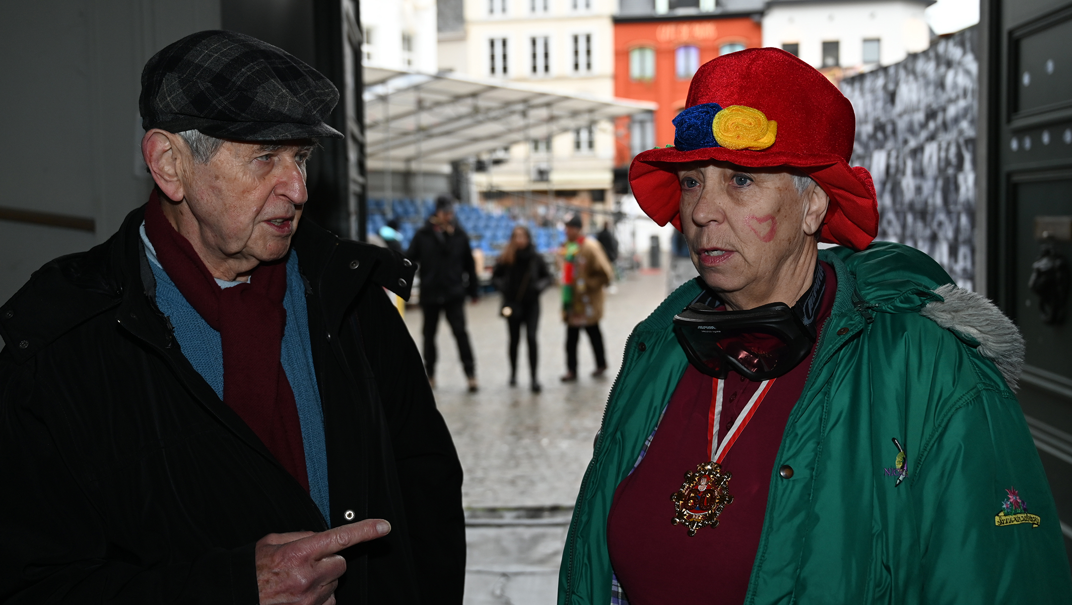 Greet Stevens, right, speaking to Rudi Roth, a Belgian-Jewish journalist, while wearing blackened goggles to protest perceived anti-Semitism at the carnival of Aalst, Belgium on Feb. 23, 2020. (Cnaan Liphshiz)
