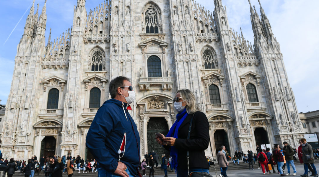 Man and woman standing outside the Milan Cathedral with protective masks and sanitizing gels in Milan, Italy on Feb. 23,2020 (Andrea Diodato/NurPhoto via Getty Images)