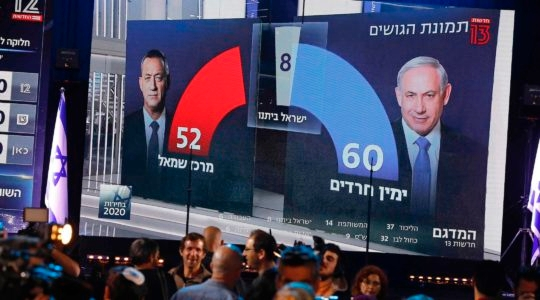 A TV screen broadcasts the exit poll results of the Israeli election in Tel Aviv on March 2, 2020. After more than a year of political deadlock, Benjamin Netanyahu and Benny Gantz have agreed to form a government together. (Menahem Kahana/AFP via Getty Images)