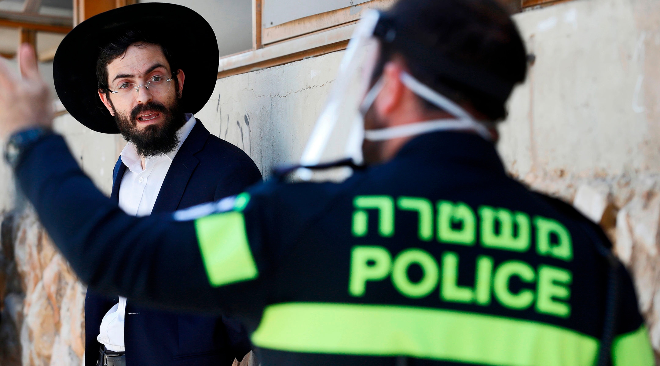 Israeli police officer speaking to a haredi student in Bnei Brak, Israel on April 2, 2020.(Jack Guez/AFP/Getty Images)