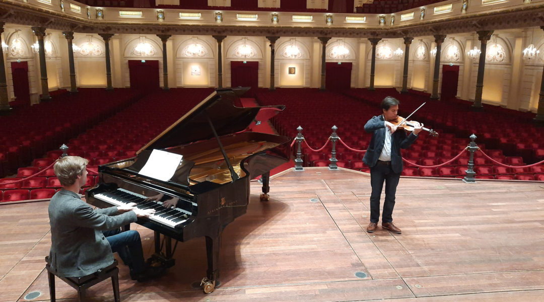 Pianist Marc Wielart and violinist Eduardo Paredes Crespo playing Israel's national anthem at the Concergebouw hall in Amsterdam, the Netherlands in April 2020. (Courtesy of Barry Mehler)