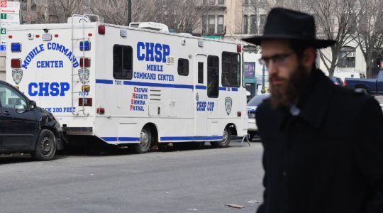 An Orthodox Jew walks past a Crown Heights Shmira Patrol security vehicle in the Brooklyn neighborhood of Crown Heights on February 27, 2019. (Angela Weiss//AFP via Getty Images)