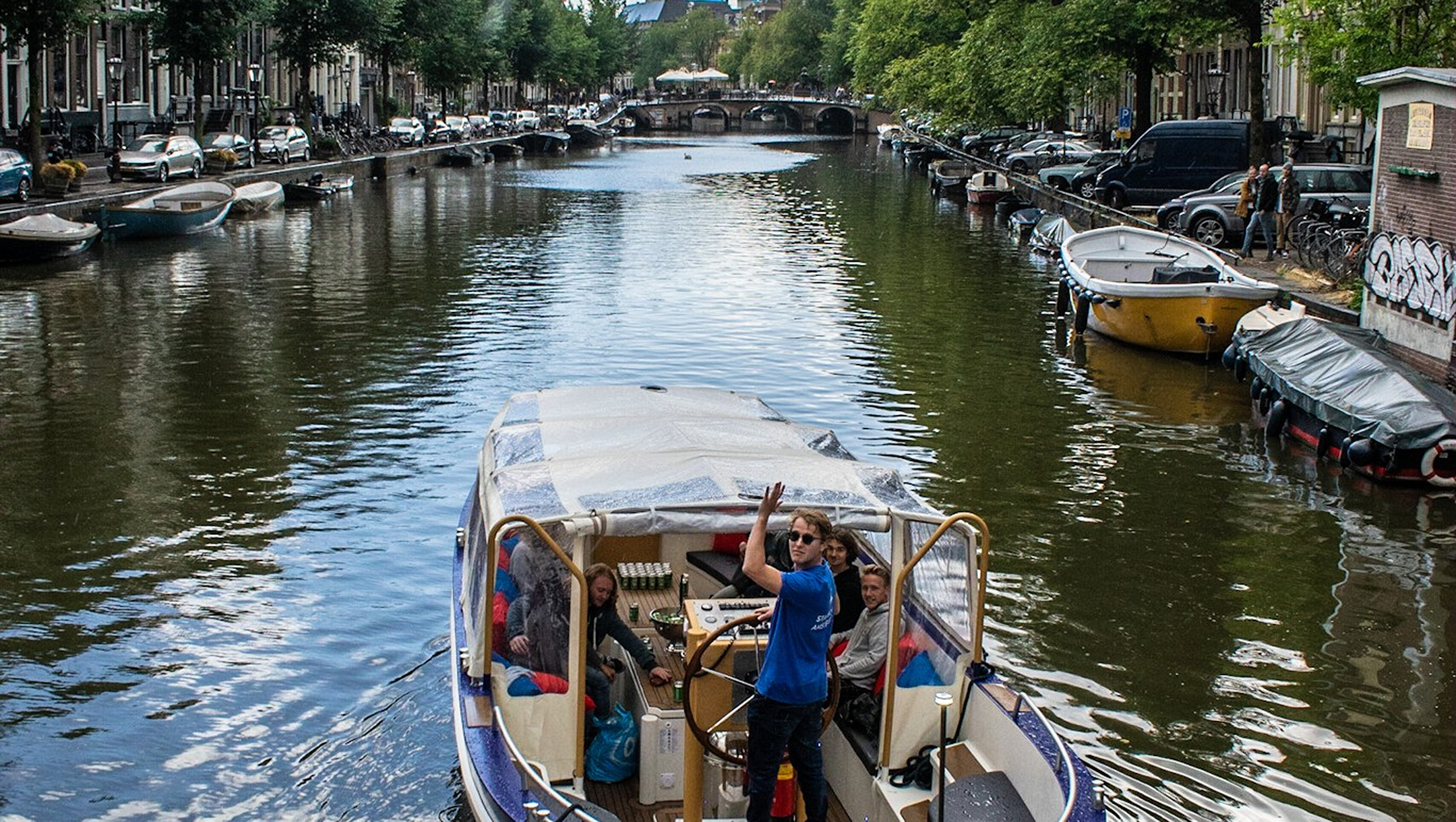 A boat belonging to the We Are Amsterdam canal tour operator sails in the center of Amsterdam, the Netherlands in 2019. (Courtesy of We Are Amsterdam)