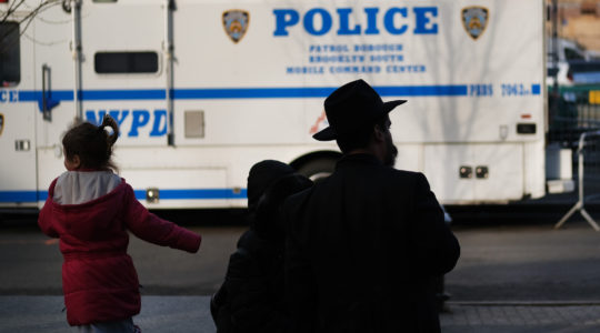 A man and girl in the Crown Heights neighborhood of Brooklyn stand opposite a police van on Dec. 31, 2019. Brooklyn was the location of more than one third of the total anti-Semitic assaults committed last year, according to the Anti-Defamation League. (Spencer Platt/Getty Images)