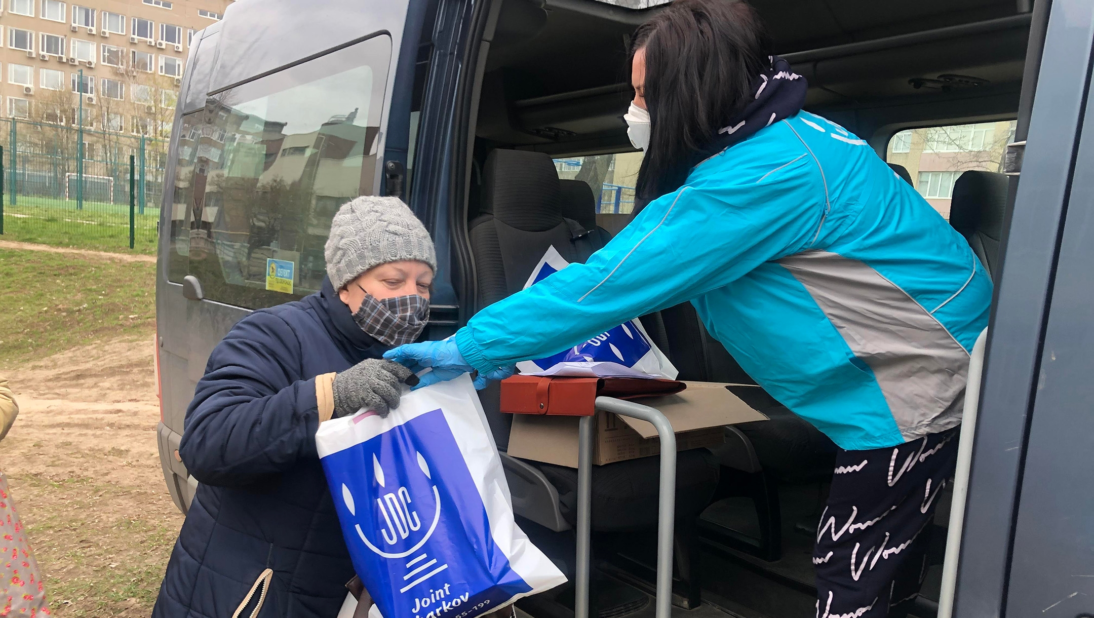 An employee of the American Jewish Joint Distribution Committee, right, hands out an aid package to a Jewish woman in Kharkiv, Ukraine during the coronavirus pandemic in March 2020. (Courtesy of JDC)