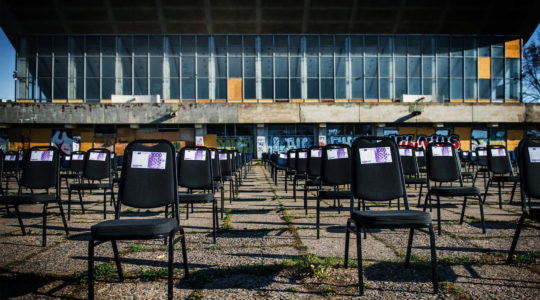 Chairs with fake money notes standing next to the decaying Palace of Concerts and Sports of Vilnius, Lithuania on May 1, 2020. (Courtesy of the display's organizers)