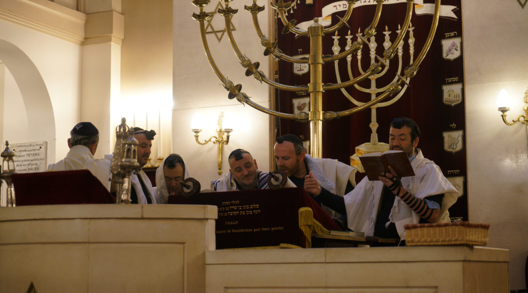Rabbi Michael Azoulay, second from right, reading the Torah with congregants at the synagogue of Neuilly-sur-Seine, Dec. 11, 2017. (Cnaan Liphshiz)