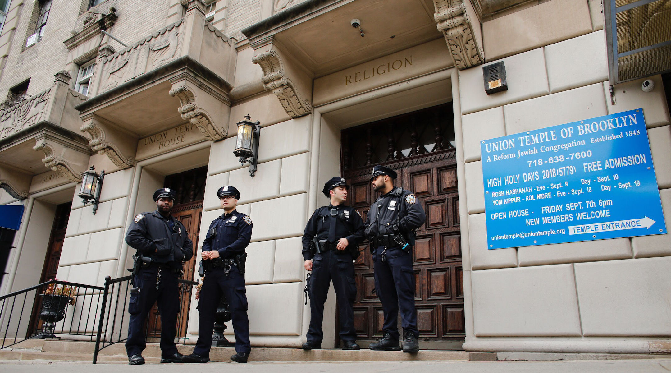 NYPD officers stand guard at the door of the Union Temple of Brooklyn, after it was grafittied, in New York City on November 2, 2018. (Kena Betancur/AFP via Getty Images)