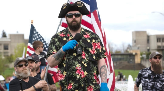 Matt Marshall of the right-wing group Washington State Three Percent (3%), and clad in the Boogaloo uniform of a Hawaiian shirt, speaks at a 'Hazardous Liberty! Defend the Constitution!' rally to protest the stay-at-home order, at the Capitol building in Olympia, Washington on April 19, 2020. (Karen Ducey/Getty Images)
