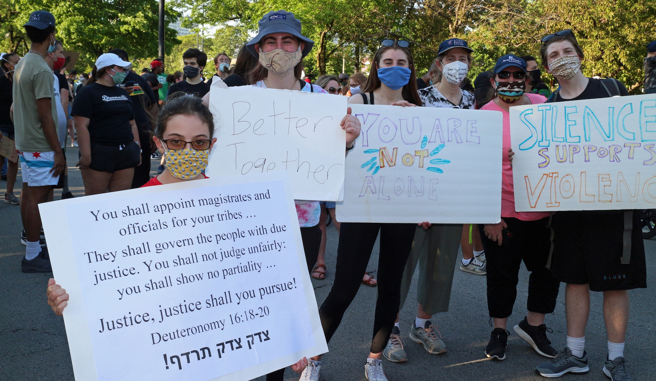 Demonstrators hold up signs at the protest. (Ariel Tesher)