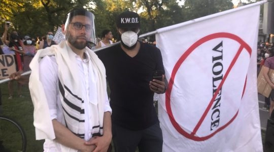 Rabbi Ari Hart, wearing a prayer shawl and face shield, stands with another protester at the interfaith demonstration in memory of George Floyd and protesting systemic racism in Chicago on June 2, 2020. (Courtesy of Hart)