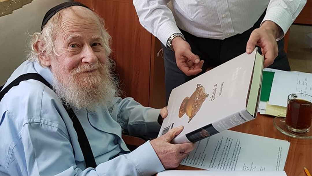 Rabbi Adin Even-Israel (Steinsaltz) inspects at his Jerusalem home an English-language translation of the Talmud based on his annotations on June 4, 2018. (Wikimedia Commons/SoInkleined)