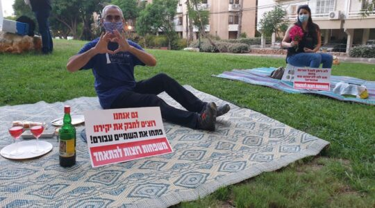 "Israelis protest being separated from their significant others outside the residence of the foreign minister by having solo romantic picnics on the eve of Tu B'Av, the Jewish day celebrating love. The signs read, ""We also want to embrace our loved ones. Open the skies for them. Families want to be together."" (Courtesy of Plia Kettner)"