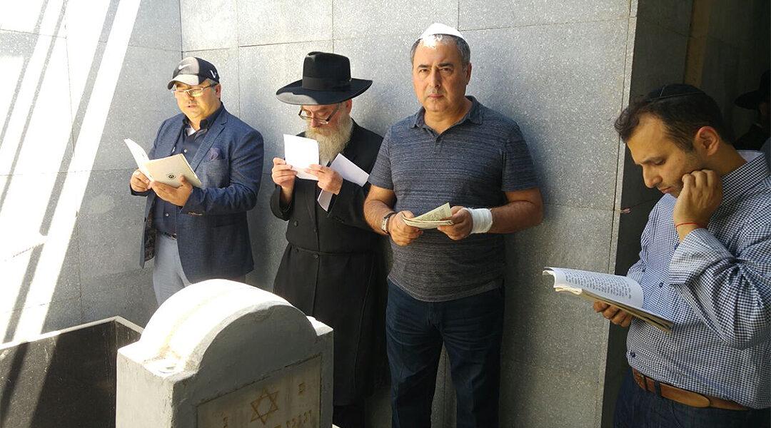 Men pray around the grave site of Levi Yitzchak Schneerson in Almaty, Kazakhstan in 2016. (Courtesy of Chabad Kazakhstan)