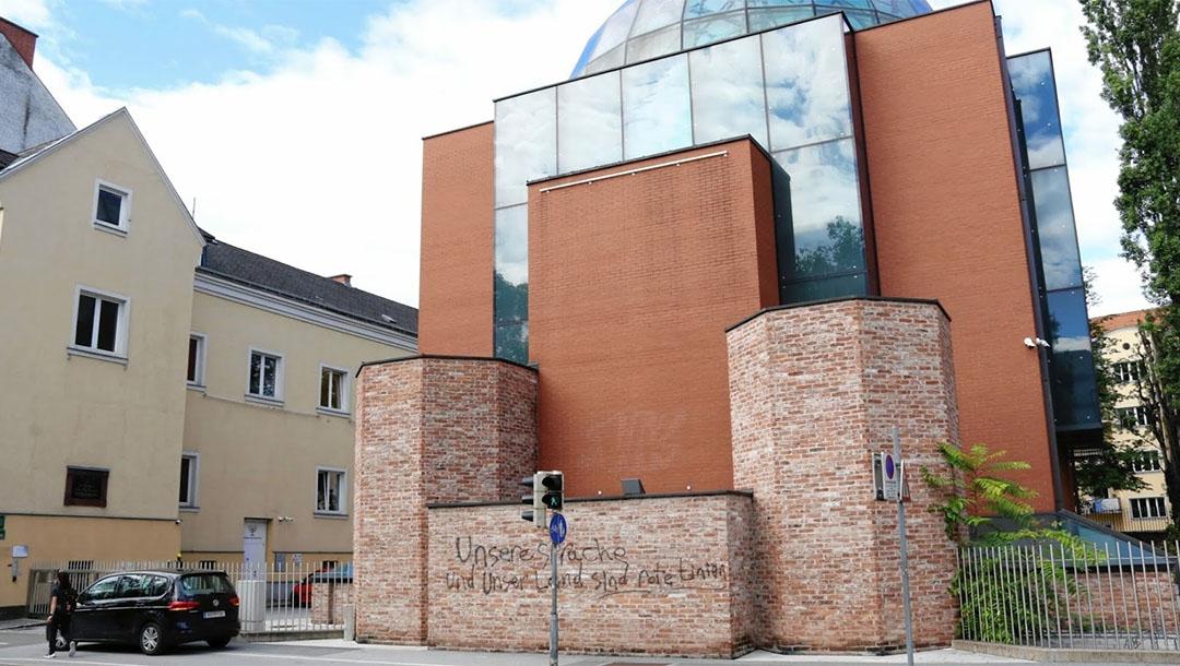 A man walks past the defaced facade of the synagogue of Graz, austria on Aug. 19, 2020. (Christian Jauschowetz)