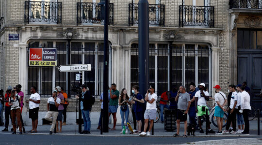Pedestrians watch police outside a bank in Le Havre, France, where a hijacker has taken several hostages demanding the freedom of Palestinians in Israel on Aug. 7, 2020. (Sameer Al-Doumy/AFP via Getty Images)