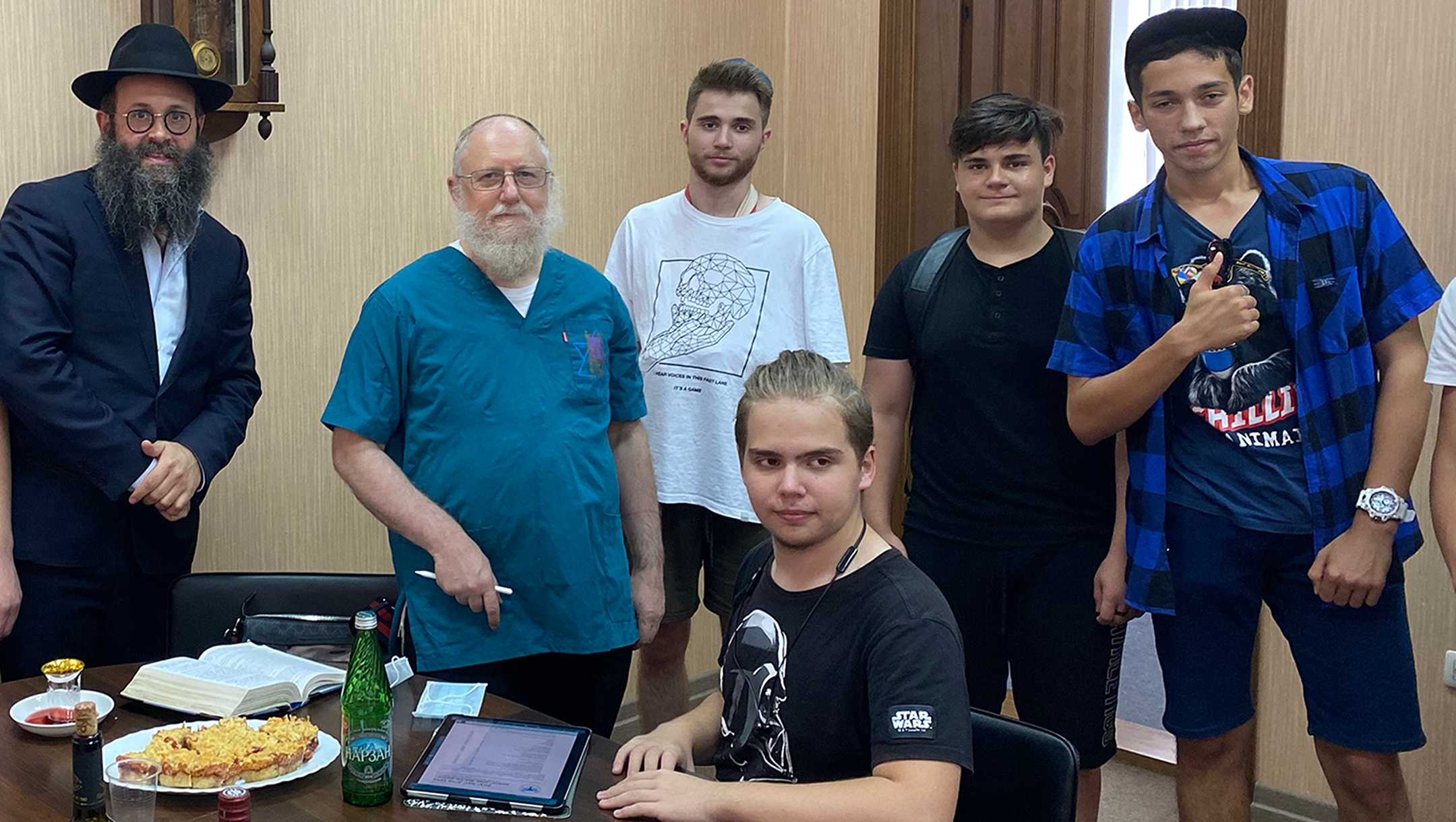 Rabbi Chaim Danzinger, left, introduces Dr. Yeshaya Shafitto younger Jews awaiting circumcision at the synagogue of Rostov-on-Don, Russia on July 27, 2020. (Courtesy of the Jewish Community of Rostov.)