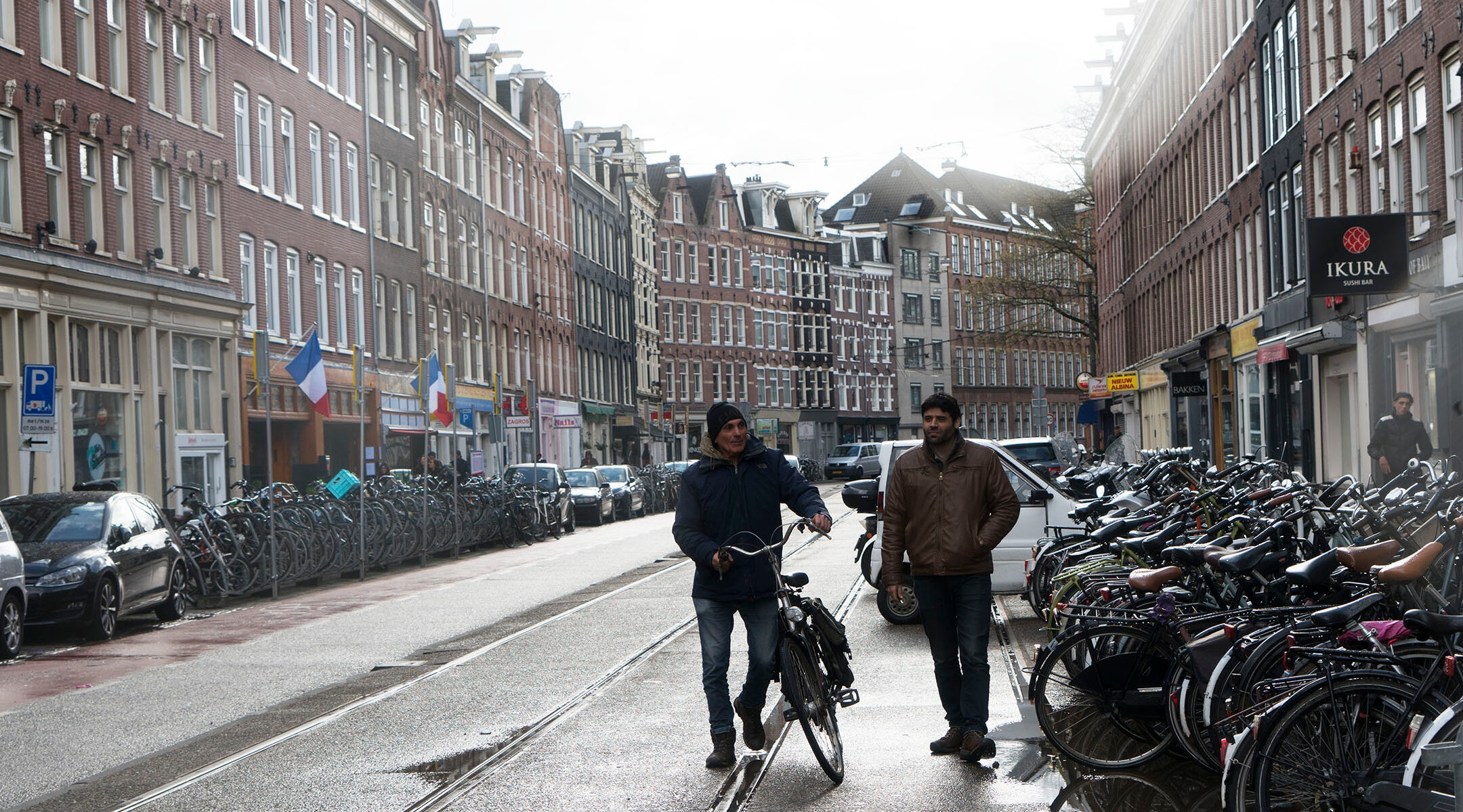 Two men walk down a street in a residential area of Amsterdam, the Netherlands on April 23, 2017. (Cnaan Liphshiz)