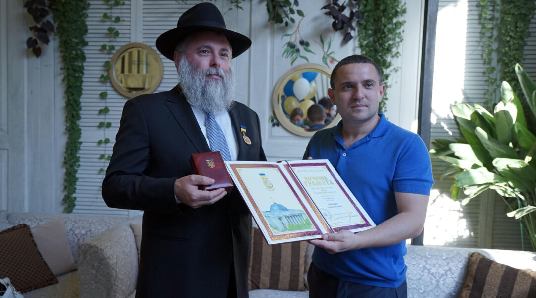 Rabbi Yonatan Markovitch, left, holds up a medal and a certificate he received at the parliament of Ukraine in Kyiv on Sept. 7, 2020. (Courtesy of Markovitch)
