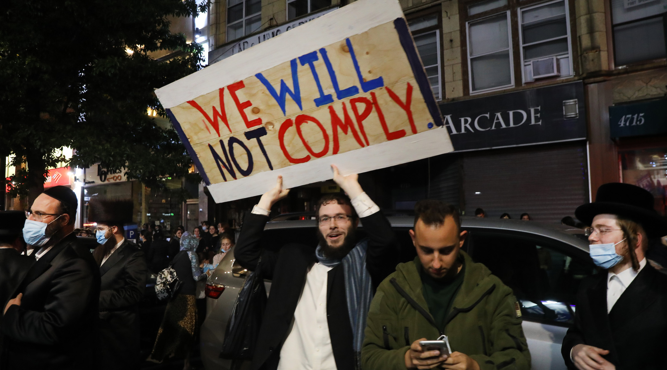 """A man holds up a sign reading """"We will not comply"""" during recent protests in Borough Park against public health restrictions on October 7. (Spencer Platt/Getty Images)"""
