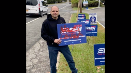 Congressional candidate Josh Eisen holds a campaign sign tagged with anti-Semitic graffiti. (Screenshot from News12)