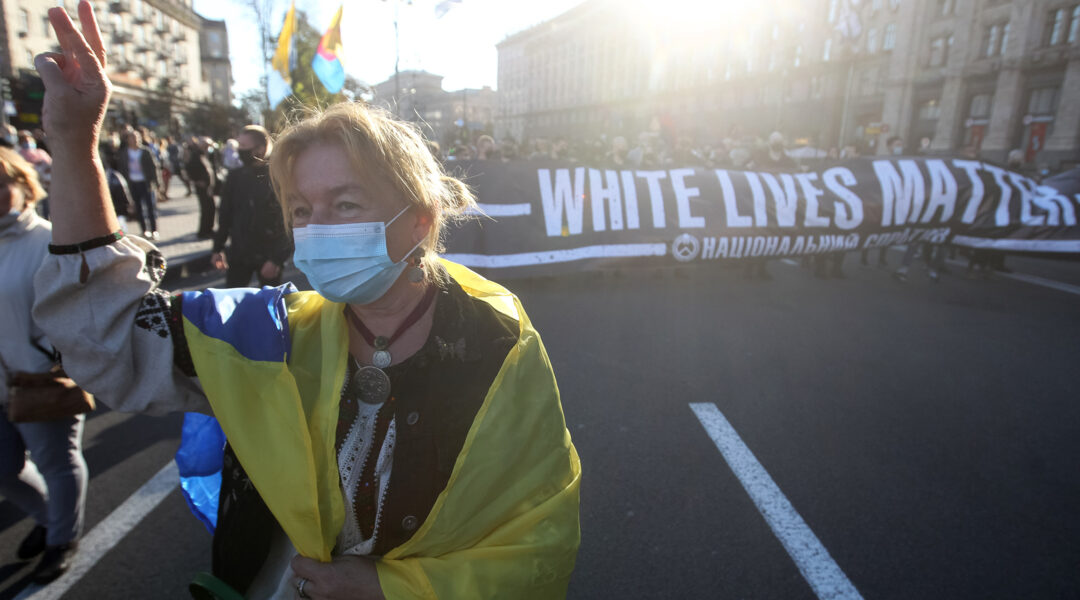 A woman wearing a Ukrainian flag performs an ultranationalist gesture while marching at an event honoring collaborators with Nazi Germany in Kyiv, Ukraine on Oct. 14, 2020. (STR/NurPhoto via Getty Images)