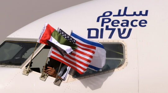 "An Israeli El Al airplane flying the flags of Israel, the United Arab Emirates and the United States, and bearing the word ""peace"" in Arabic, English and Hebrew, arrives at the Abu Dhabi airport after flying from Tel Aviv on August 31, 2020. (Karim Sahib/AFP via Getty Images)"