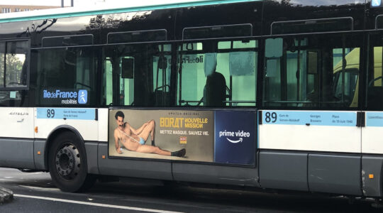 A RATP bus with a billboard of Sacha Baron Cohen wearing a ring with the word Allah on it moves through Paris, France on Nov. 2, 2020. (Courtesy of @firehairedreamr/Twitter)