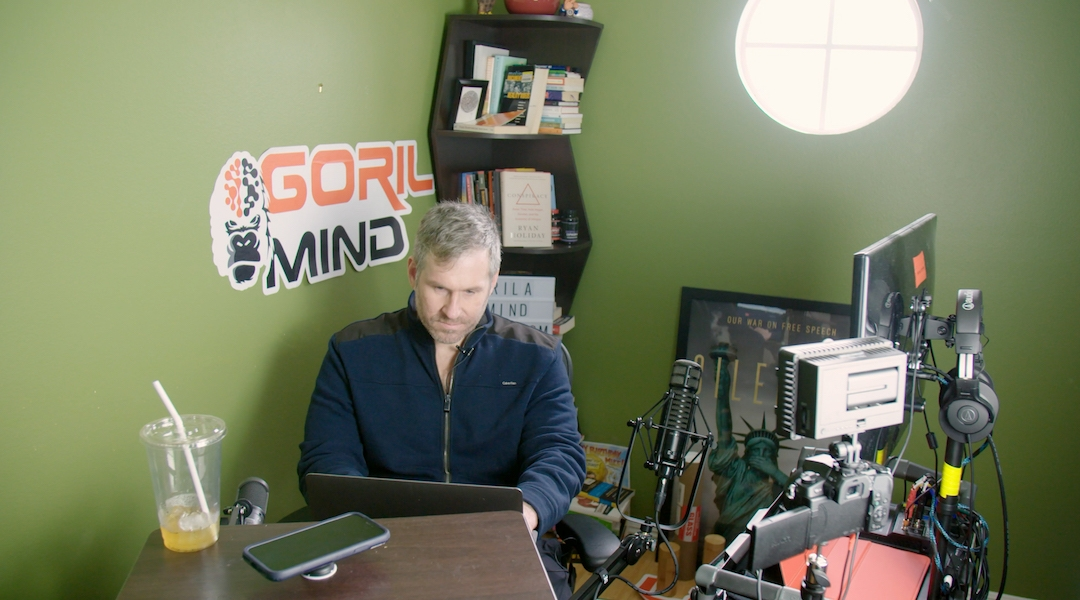 Mike Cernovich, a conspiracy theorist, works at his laptop in the documentary. (Courtesy of Lombroso)