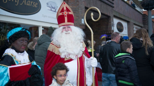 A child poses for a photo with a woman dressed as Black Pete and a man portraying Saint Nicholas in northern Amsterdam, the Netherlands on Nov. 16, 2019. (Cnaan Liphshiz)