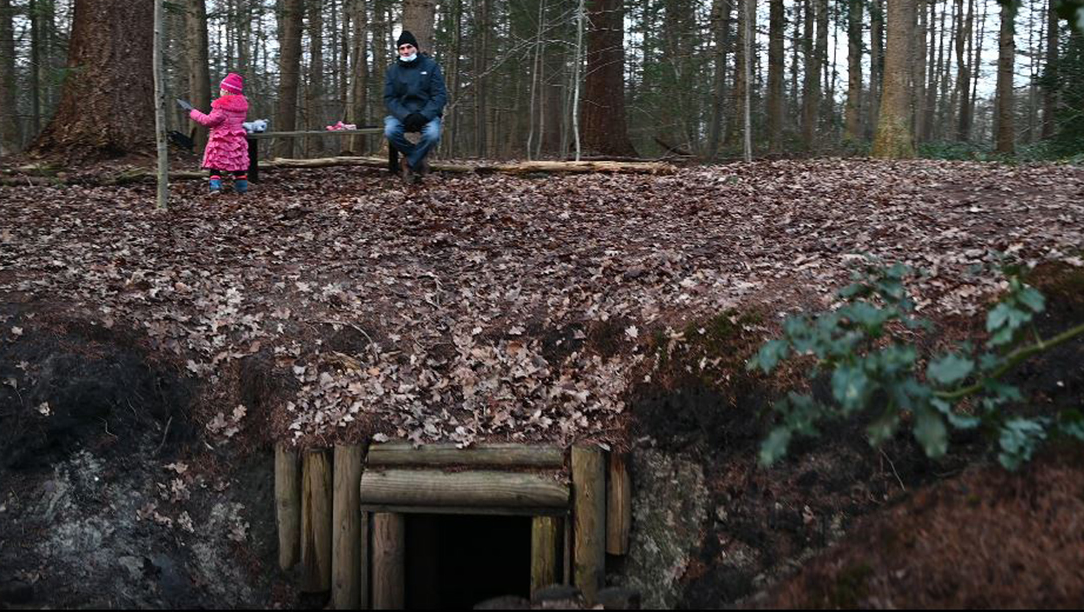 A Dutch child plays near her grandfather atop a reconstructed dugout for Jews in hiding in Nieuwlande, the Netherlands on Jan. 25, 2021. (Cnaan Liphshiz)