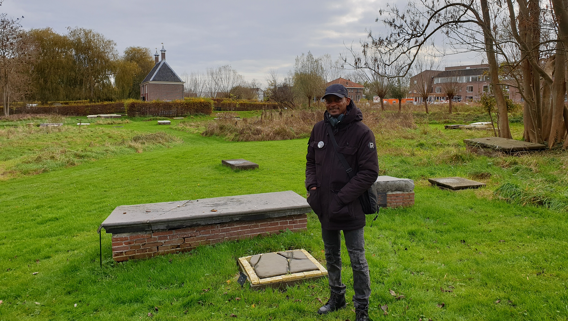 Sergio Berrenstein stands next to the grave of Elieser and his master at the entrance to the Jewish cemetery in Ouderkerk aan de Amstel, the Netherlands on Nov. 20, 2020. (Cnaan Liphshiz)