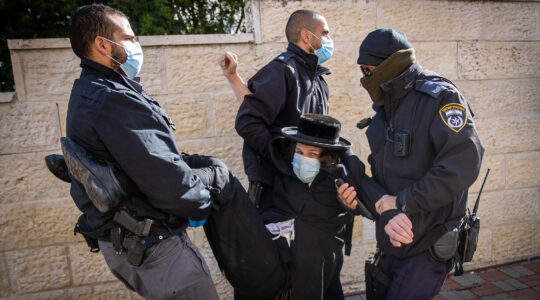 Police officers carry a protester away during raid on a Jerusalem yeshiva that remained open in violation of COVID-19 restrictions on January 19, 2021. (Yonatan Sindel/Flash90)