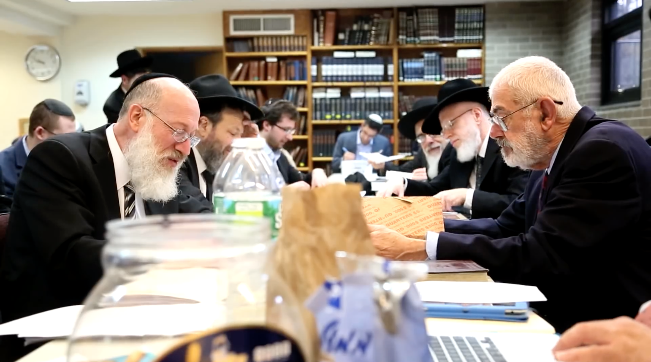 Rabbi Mordechai Willig, left, executes the 2015 sale of hametz to John Brown, right. Brown died this year after decades of buying hametz from thousands of American Jews each year before Passover. (Josh Weinberg/screen shot from YouTube)