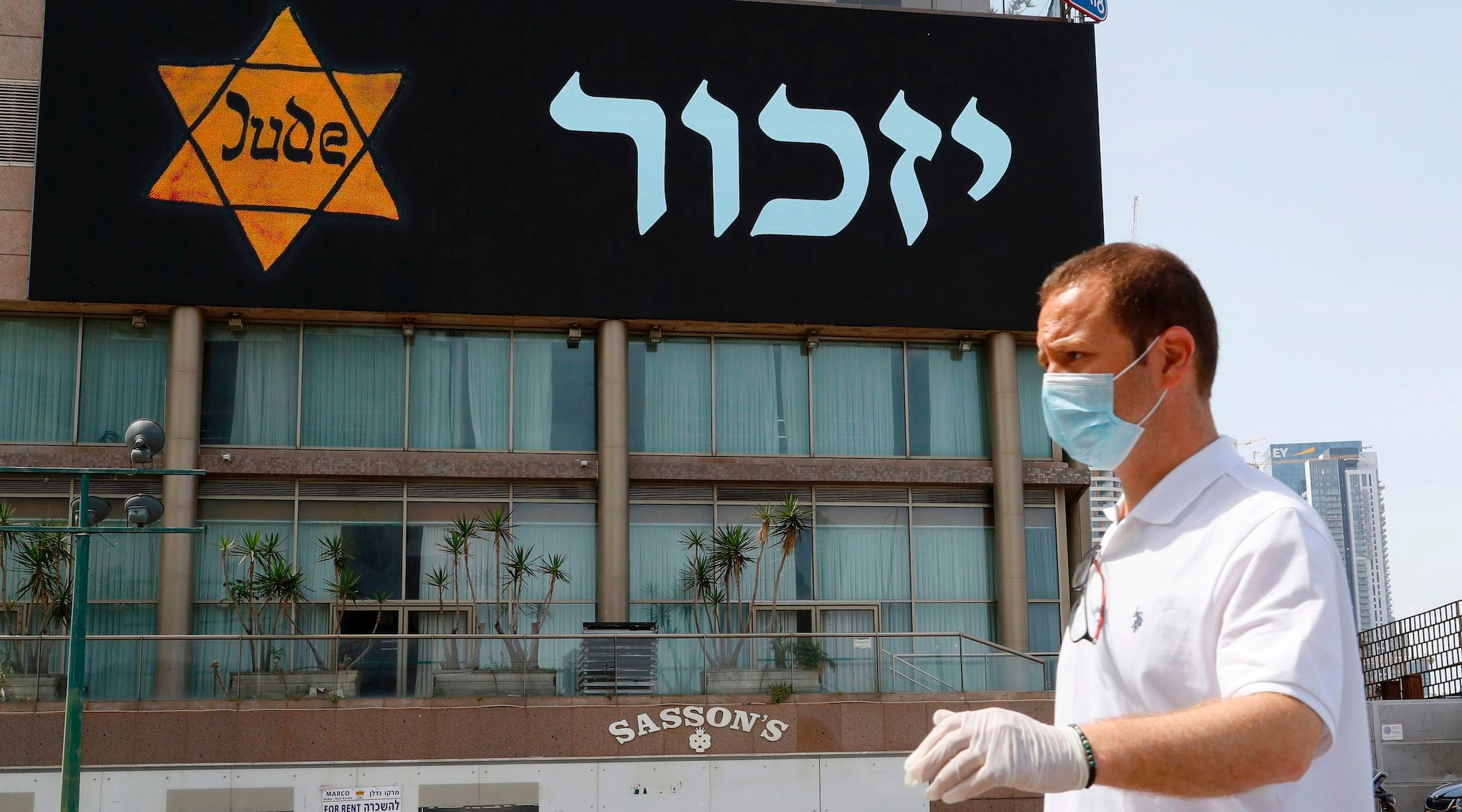 A man in a mask and protective gear stands near a banner depicting a Holocaust-era yellow Star of David in Tel Aviv on April 21, 2020. (Jack Guez/AFP via Getty Images)