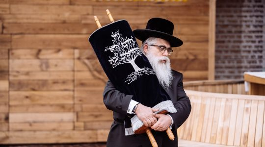 Ukrainian Chief Rabbi Ya'akov Dov Bleich holds a Torah scroll during the opening ceremony in Kyiv, Ukraine on April 7, 2021 of a synagogue on the site of the Babi Yar 1941 massacre of Jews. (Babyn Yar Holocaust Memorial Center)