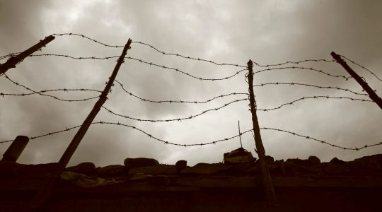 Barbed wire fence against a dark sky