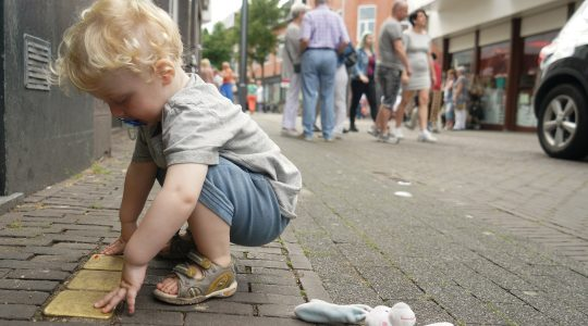 The son of JTA's Europe correspondent pictures here when he was nearing his 2nd birthday, examines a memorial cobblestone for murdered Dutch Jews in Heerlen, the Netherlands on July 29, 2017. (Cnaan Liphshiz)