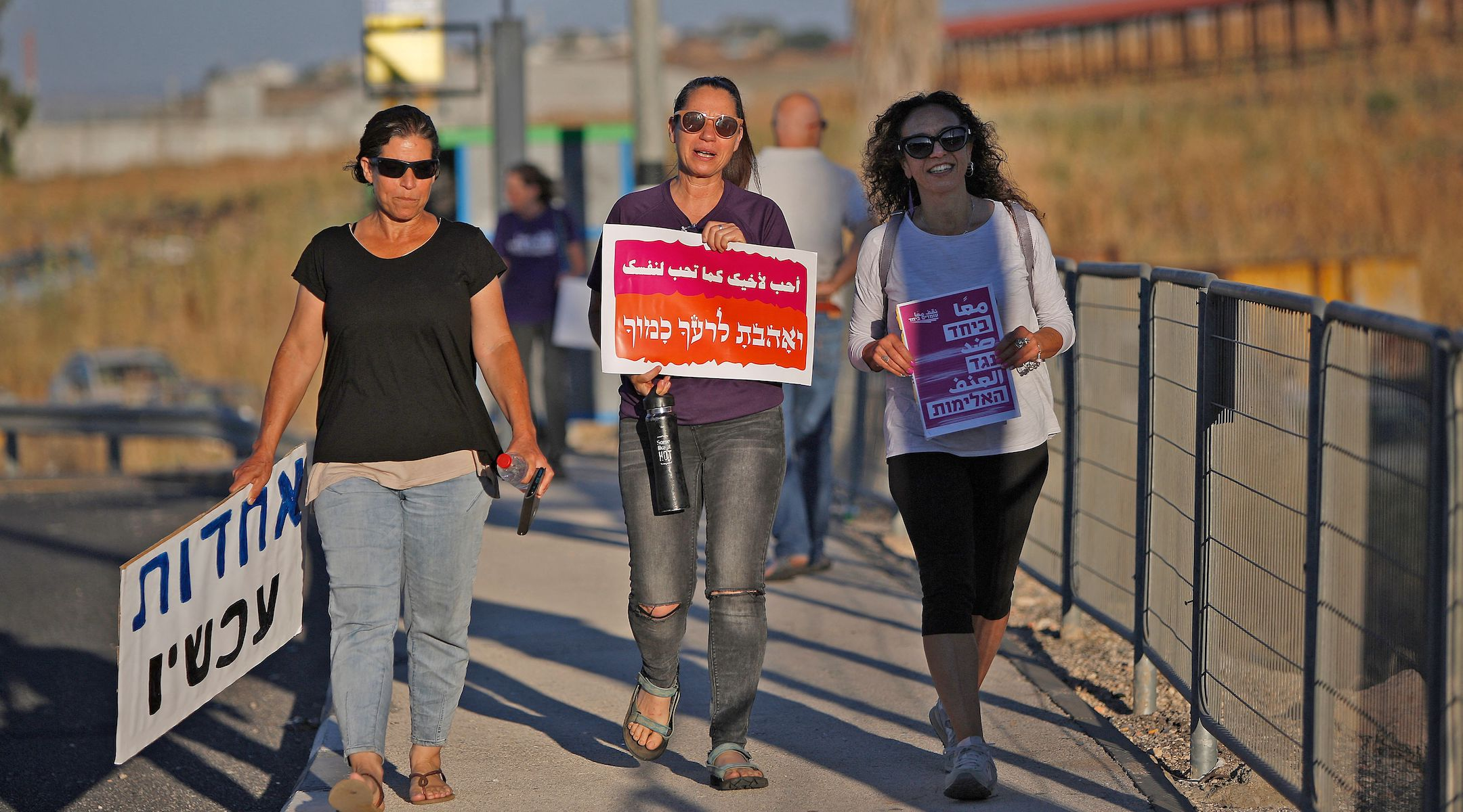 """Three women walk in a demonstration for coexistence in northern Israel on May 11, 2021. The sign in the middle says """"Love your neighbor as yourself."""" (Jalaa Marey/AFP)"""