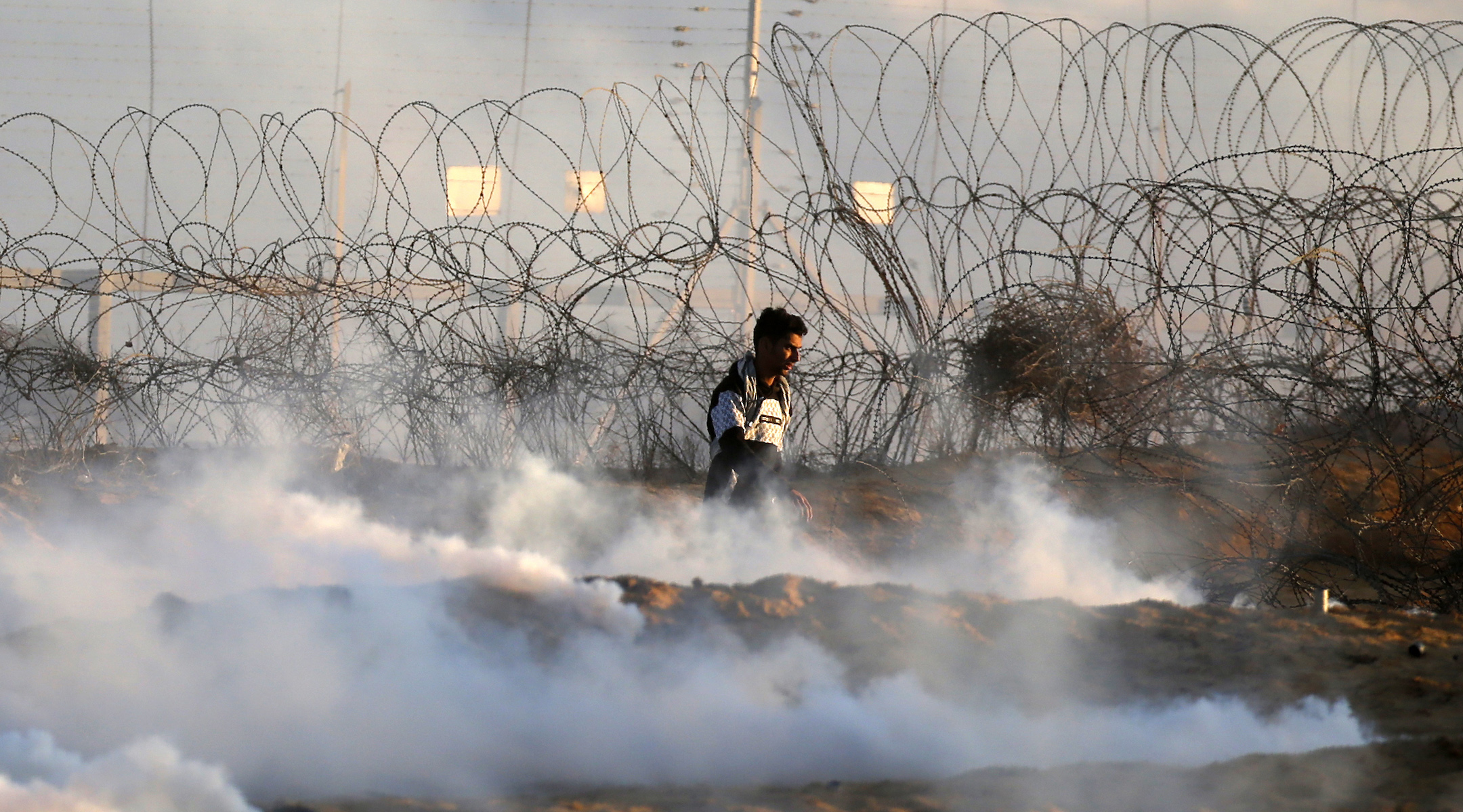A Palestinian demonstrator walks amidst tear gas smoke fired by Israeli forces during a protest near the Israel-Gaza border fence in the southern Gaza Strip, on December 27, 2019. (Said Khatib/AFP via Getty Images)