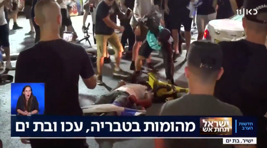 A man beats someone lying prone on the ground in the Israeli city of Bat Yam, amid interethnic violence across Israel. (Screenshot)