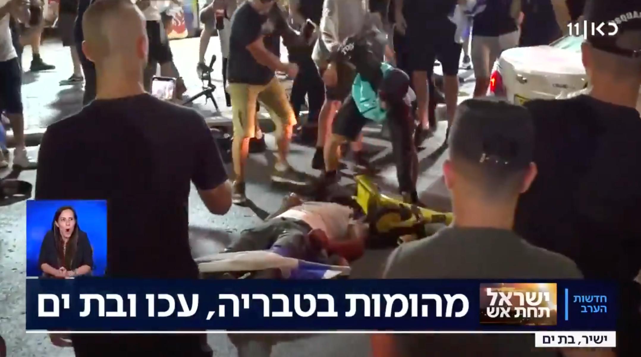 A man beats someone lying prone on the ground in the Israeli city of Bat Yam, amid interethnic violence across Israel. (Screenshot)