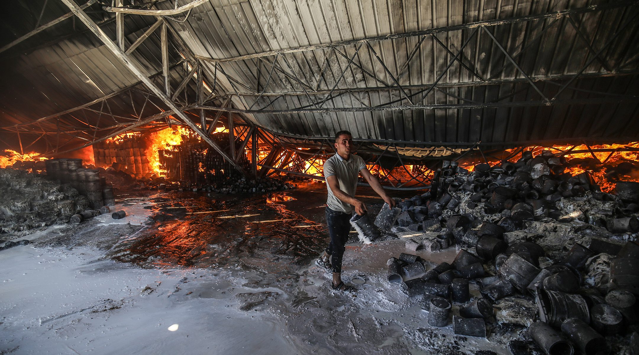 Firefighters attempt to extinguish a fire at a warehouse which was hit during an Israeli airstrike in Rafah, in the southern Gaza Strip, on May 18, 2021. (Abed Rahim Khatib/Flash90)